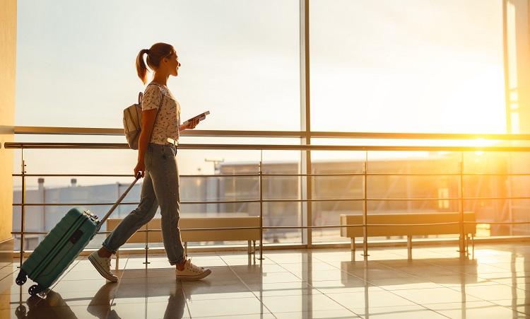 Frau mit Koffer am Flughafen auf dem Weg zum Gate